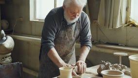 Den erfarna manliga keramikern är blanda och knåda lera på worktablen, medan arbeta i litet seminarium med professionelln arkivfilmer