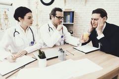 Den erfarna neurologen ger exponeringsglas för den vuxna mannen av att dricka med blandningen av huvudvärker arkivbilder