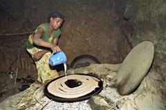 Den etiopiska kvinnan bakar injera på wood brand arkivfoton