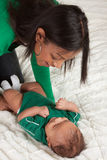 Den etniska modern som leker med henne, behandla som ett barn pojkesonen på underlag Royaltyfri Fotografi