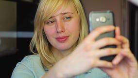 Den europeiska blonda flickan med olika ögon tar selfie på telefonen, heterochromia stock video