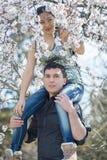 Den europeiska grabben som bär hans asiatiska flicka, i att blomstra, parkerar Arkivbild