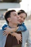 Den europeiska grabben som bär på, knuffar hans asiatiska flicka Arkivbild