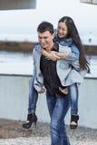 Den europeiska grabben som bär på, knuffar hans asiatiska flicka Royaltyfri Bild