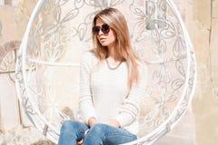 Den europeiska stilfulla hipsteren för den unga kvinnan i solglasögon med en briljant halsband i stilfull jeans i en stucken tröj royaltyfria foton