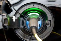 Den EV-bilen eller elbilen på uppladdningsstationen med tillförselen för maktkabel pluggade arkivfoton