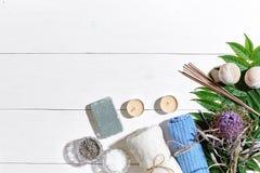 den exotiska brunnsorten för blommamassageprodukter stenar handduken Badsalt, torra blommor lavendel, tvål, stearinljus och handd Arkivbilder