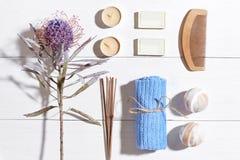 den exotiska brunnsorten för blommamassageprodukter stenar handduken Badsalt, torra blommor lavendel, tvål, stearinljus och handd Royaltyfria Bilder
