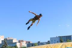 Den extrema idrottsman nen hoppar på rullskridsko Arkivfoto