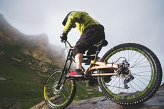 Den extrema mannen för mountainbikesportidrottsman nen i hjälmridning mot en bakgrund av vaggar utomhus livsstil prov arkivfoto