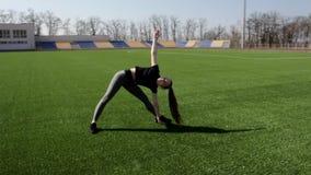Den färdiga aktiva godan som ser den unga kvinnan lägger benen på ryggen sträcka övning för att värma muskler som upp utarbetar y arkivfilmer