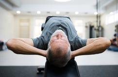 Den färdiga höga mannen i idrottshallen som arbetar hans abs som gör knastrar Royaltyfri Fotografi