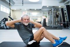 Den färdiga höga mannen i idrottshallen som arbetar hans abs som gör knastrar Royaltyfri Bild