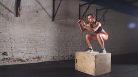 Den färdiga idrotts- kvinnan boxas hopp i den öde fabriksidrottshallen Den intensiva övningen är delen av hennes dagliga arga kon lager videofilmer