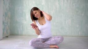 Den färdiga idrotts- kvinnan smsar sms i sportidrottshall på telefonen Stående av en lycklig konditionkvinna som använder smartph lager videofilmer