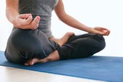 Den färdiga kvinnan i en meditativ yoga poserar på idrottshallen Royaltyfri Fotografi