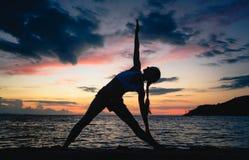 Den färdiga kvinnan som öva den fördjupade triangelyogan, poserar på en drömlik strand Arkivfoto