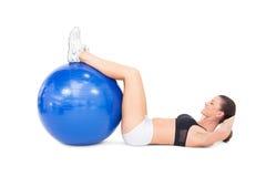 Den färdiga kvinnan som framkallar hennes abs som använder övning, klumpa ihop sig Arkivfoton