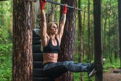 Den färdiga kvinnan som gör det hängande benet, lyfter absmuskler övar på den horisontal stången som utanför utarbetar Royaltyfri Fotografi