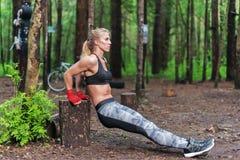 Den färdiga kvinnan som gör tricepsdopp på, parkerar Konditionflicka som utomhus övar med egen bodyweight Arkivfoto