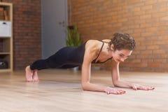 Den färdiga kvinnan som gör yoga- eller pilatesövningsanseende i planka, poserar den kallade phalankasanaen som utarbetar på golv Royaltyfri Fotografi
