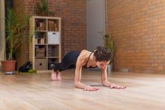 Den färdiga kvinnan som gör yoga- eller pilatesövningsanseende i planka, poserar den kallade phalankasanaen som utarbetar på golv Royaltyfri Foto