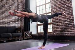 Den färdiga kvinnan som gör yoga för krigare tre, poserar anseende på ett ben som framåtriktat lutar med bröstkorgen, och benet s Arkivbilder
