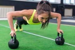 Den färdiga kvinnan som ungt göra skjuter, ups övning med hantlar i idrottshallen Royaltyfri Fotografi