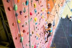 Den färdiga kvinnan vaggar klättring inomhus arkivfoton