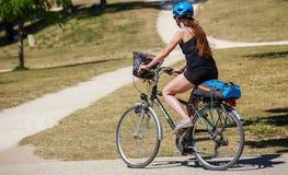 Den färdiga kvinnaridningcykeln parkerar in royaltyfria foton