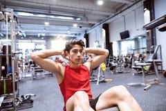 Den färdiga latinamerikanska mannen i idrottshallutbildning, funktionsduglig abs som gör knastrar Royaltyfri Fotografi