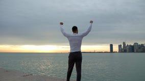 Den färdiga muskulösa mannen går och stoppar på stranden med hans armar i luften Stad, hav och soluppgång på bakgrunden Han är a stock video