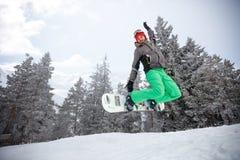 Den färdiga snowboarderen som hoppar med snowboarden på, skidar terräng royaltyfri bild