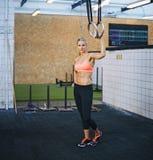 Den färdiga unga kvinnan på idrottshallen med gymnasten ringer Royaltyfria Foton