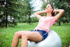 Den färdiga unga kvinnan som gör sitta-UPS på en konditionboll som in övar, parkerar arkivfoto