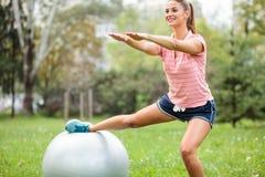 Den färdiga unga kvinnan som gör squats med ett ben som vilar på en konditionboll, armar sträckte rakt framåt royaltyfri foto