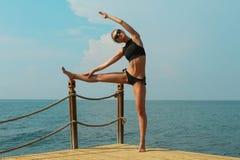 Den färdiga unga kvinnan sträcker fotografering för bildbyråer