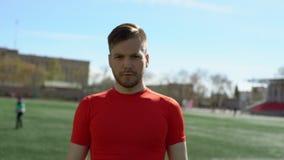 Den färdiga unga mannen går på sportstadiongräsmatta stock video