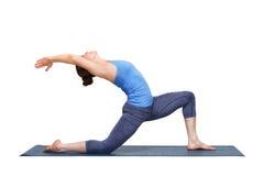 Den färdiga yoginikvinnan öva yogaasanaen Anjaneyasana arkivfoto