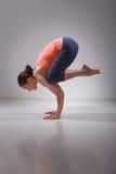Den färdiga yoginikvinnan öva yogaasanaen Bakasana royaltyfri bild