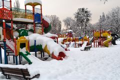 Den färgade lekplatsen i vintern, blickar övergav under snö royaltyfria foton