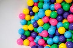 Den färgade plast- bollen i ett kaotiskt sätt i barns lekrum förbereder sig för partiet, färgrika bollar på sidoram av vit backgr royaltyfria foton