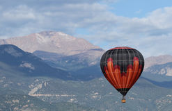 Den färgrika ballongen för varm luft som flyger över pikar, når en höjdpunkt, den Colorado våren Arkivbild
