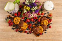 Den färgrika blandade blandningen av lösa bär, bruna kakor, mjölkar och blommor royaltyfri bild