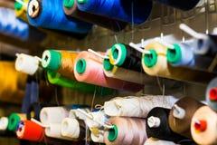 Den färgrika broderitrådrullen genom att använda i plaggbransch, rad av mångfärgat garn rullar och att sy material som säljer i m fotografering för bildbyråer