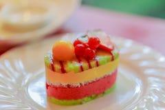 Den färgrika fruktkakasötsaken bär frukt på den vita maträtten Arkivbild
