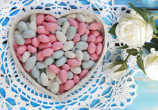 Den färgrika godisen i vit hjärta formade bunken och vita rosor på w fotografering för bildbyråer