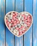 Den färgrika godisen i vit hjärta formade bunken på trätabellen arkivfoto