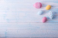 Den färgrika handen för påskägg målade på en blå bakgrund Ferievårkort arkivbilder