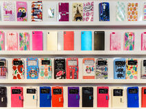 Den färgrika iPhonen och Samsung ringer fall som är till salu i mobiltelefondiversehandel royaltyfri fotografi